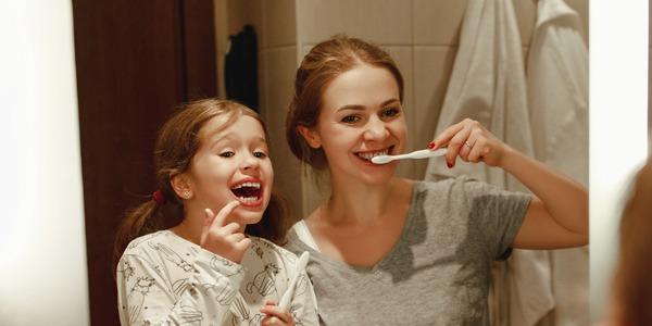Mum and daughter brushing teeth