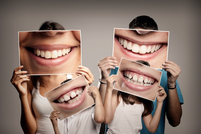 Family holding pictures of teeth