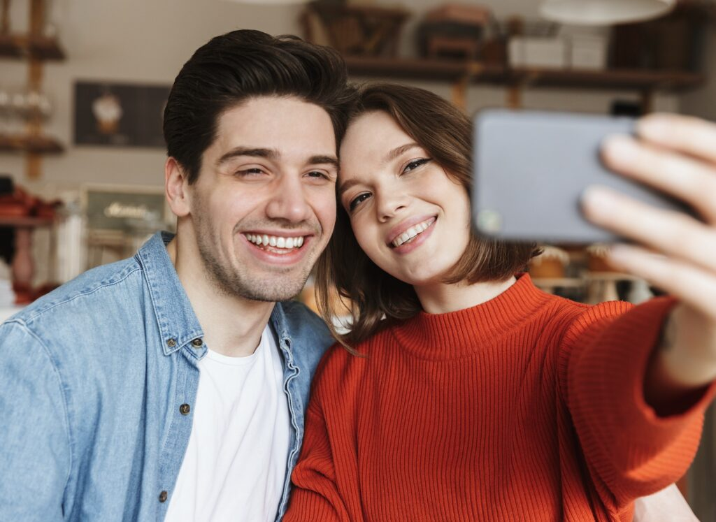 Couple taking selfie smiling with veneers